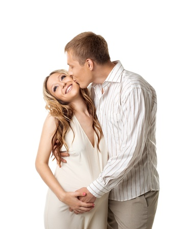 pregnant woman with husband: Young happy couple in white wait for baby - man kiss a whife Stock Photo