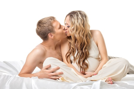 Young happy couple with pregnant woman in bed kiss together