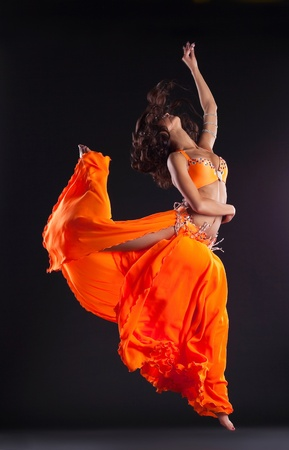 beauty dancer jump in orange oriental costume arabic style