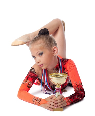 string bikini: young gymnast lay with medals and prize cup isolated