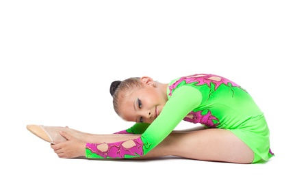 young teenager gymnast in green sit on isolated photo