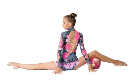 acrobacia: hermosa chica se sienta en una bola de splits con acrobacias aislados Foto de archivo
