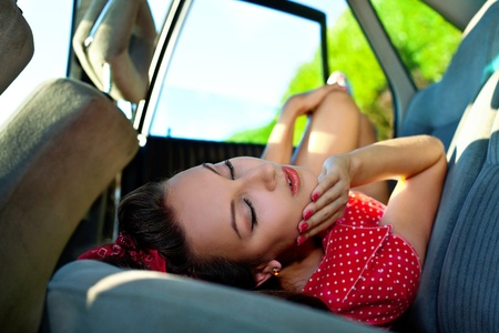 erotic dress: Young attractive woman lay in car - looc at camera