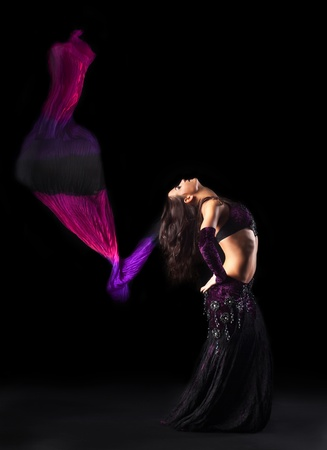 young beautiful girl in arabic costume dance with fantail and purple veil in dark photo