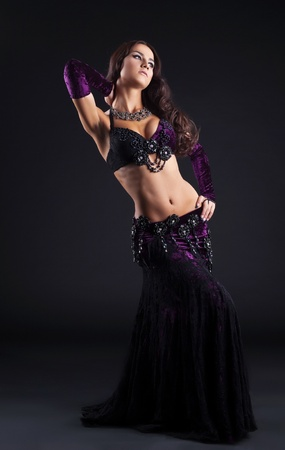 beauty girl in oriental purple arabic costume dance in dark photo