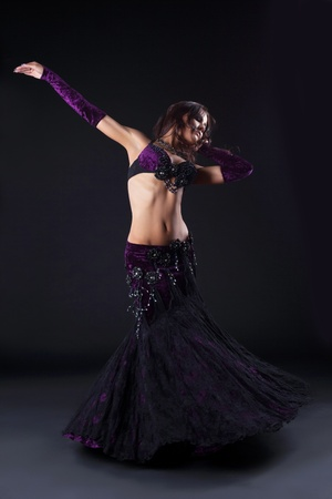 beauty girl in oriental purple arabic costume dance in dark