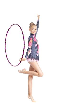 Young teenager girl doing gymnastics exercise with hoop isolated photo