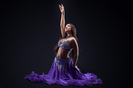 beauty young girl dance in purple veil arabic style costume in dark photo
