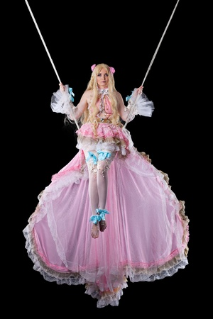Pretty girl in fary-tale doll costume fly on wire photo