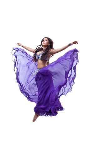 Beautiful girl  jump in dance with flying purple arabic oriental costume isolated