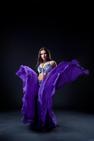 beauty young girl dance in dark with fly purple veil Stock Photo