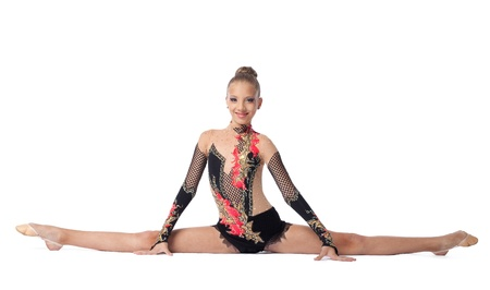 dividing: Young beautiful girl  professional gymnast sits on a splits - look at camera isolated