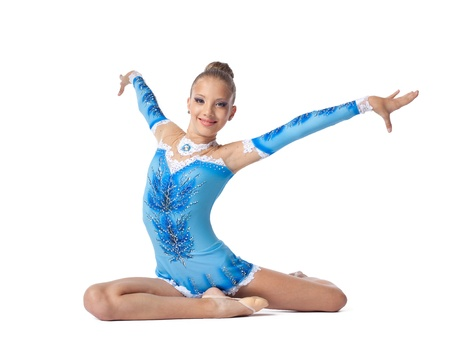Young beautiful teenager professional gymnast sits on a splits - look at camera isolated photo