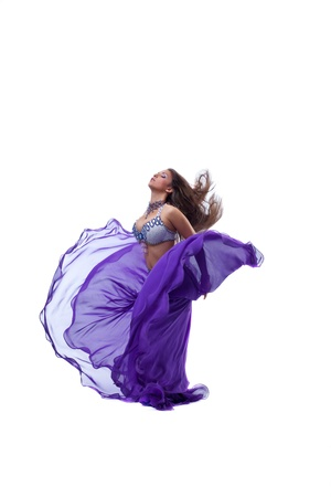 beauty young girl dance in purple arabic oriental costume with flying veil and hairs photo
