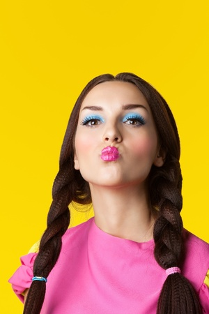 Beauty girl with funny make-up in doll costume on yellow background photo