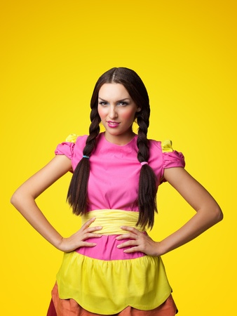 Funny girl in doll costume look seus on yellow background Stock Photo - 11139238