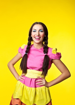 Young cute girl in doll costume and pin-up make-up smile on yellow background photo
