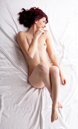 red naked girl lay on white silk bed top view, smile and confused Stock Photo - 11139249