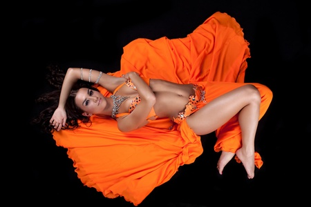 beauty young woman posing in orange traditional east style costume photo