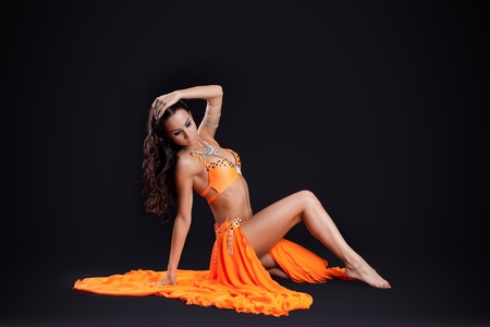 beautiful young woman sit in orange veil arabic traditional style costume photo
