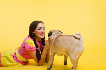 Happy girl like cute doll feed a small dog on  yellow background photo