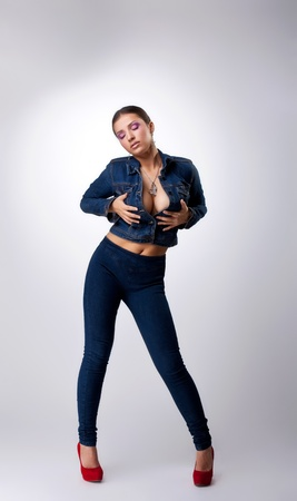Sexy young girl with huge breast posing in jeans costume - put hand on breast photo