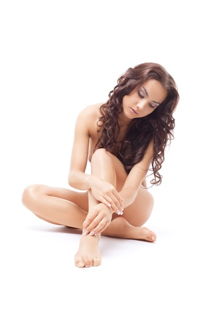 naked woman  white background: beautiful young bare woman sit on leg studio portrait isolated