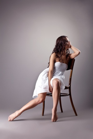 Beauty woman in white dress posing on retro chair photo