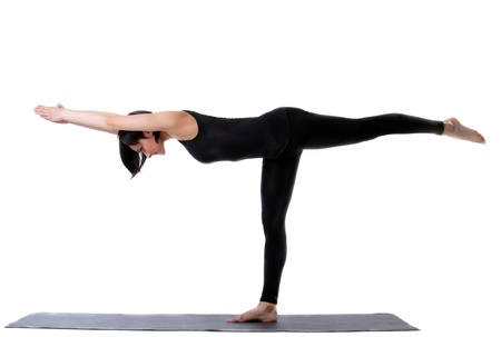 young woman training in yoga - half moon pose isolated photo