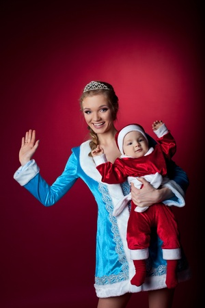 Beauty christmas girl in blue cloth play with baby santa claus near tree and gifts photo