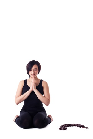 Beauty young happy woman sit in yoga asana pray with beads in meditation isolated photo
