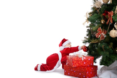 baby in santa claus costume decorate fir tree photo