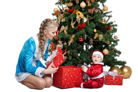 baby near christmas tree: Beauty christmas girl in blue cloth play with baby santa claus near tree and gifts
