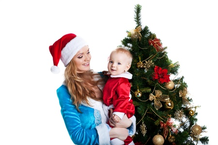 baby near christmas tree: Beauty christmas girl in blue cloth play with baby santa claus in red near fir tree  Stock Photo