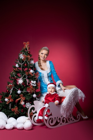 christmas girl and baby santa claus portrait on red with fir tree photo