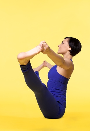 young happy woman training in funny yoga - blue on yellow photo