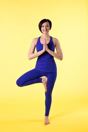 woman stand on one leg in yoga pose - blue on yellow photo
