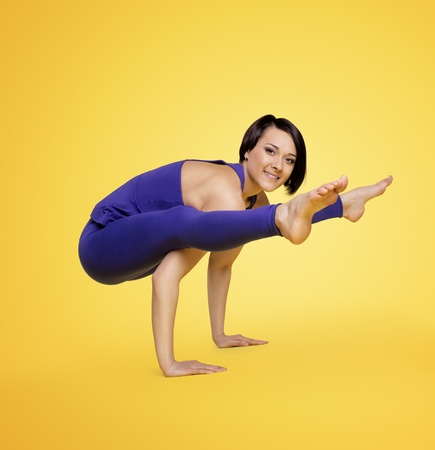 young woman exercise yoga arm balance  in blue on yellow photo