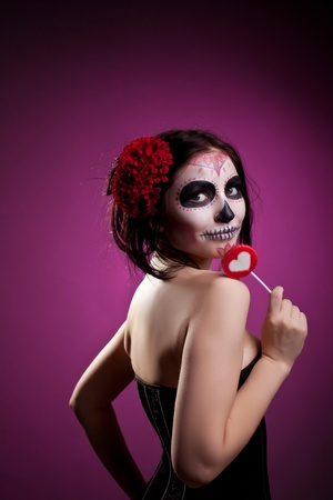 funny woman in day of the dead skull face art and heart sign candy photo