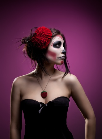 women face stare: Serious woman in day of the dead mask skull face art look aside Stock Photo