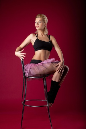 Athletic beauty young woman in dance sport costume sit on chair on red Stock Photo - 11791493