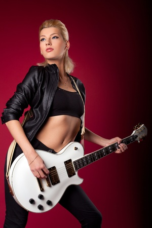 Sexy rock woman in black leather play on guitar on red background Stock Photo - 11791474