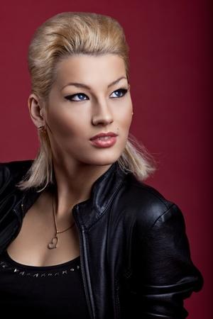 Beauty blond woman sing in black leather on red portrait like rock star Stock Photo - 11791454