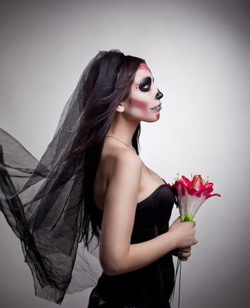 dead bride woman in skull face art mask and flowers dressed up for All Souls Day  photo