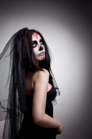 women face stare: Young woman wearing up for All Souls Day on dark