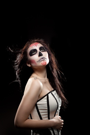 dia de los muertos: Serious woman in day of the dead mask skull face art look at camera Stock Photo