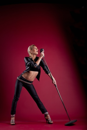 Beauty blond woman sing in black leather on red with mic like rock star photo