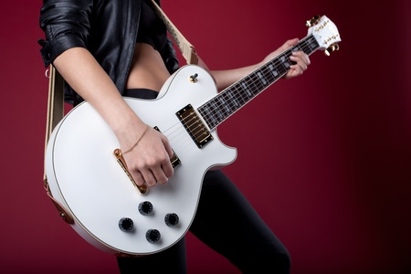 Sexy rock woman in black leather posing with electro guitar on red background photo