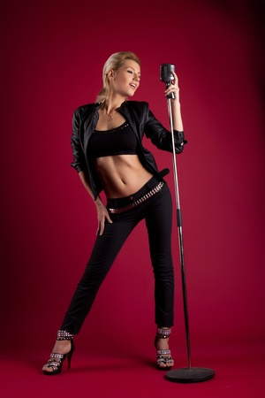 stage performer: Beauty blond woman sing in black leather on red with mic like rock star