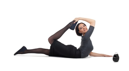 Young businesswoman lay in yoga pose before clock isolated photo